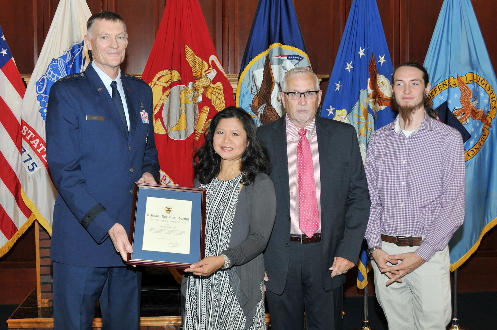 DLA Director Air Force Lt. Gen. Andy Busch (far left) presents an award to Air Force Lt. Col. Teresa Rivers for supporting her husband, Randy Taft (second from right) in his career  as son Cody Taft (far right) looks on.