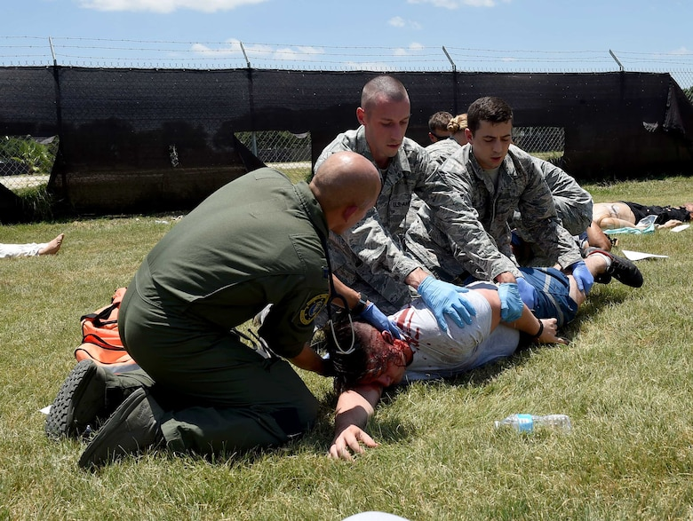 Airmen from the 59th Medical Wing roll a simulated patient on its back to better assess its injuries during a disaster response exercise July 13, 2016 at Camp Bramble on Joint Base San Antonio-Lackland, Texas. More than 50 disaster response team members participated in the exercise, which simulated an aircraft crash designed to test the team's ability to respond and treat patients in the event of a real-world incident. (U.S. Air Force photo/Staff Sgt. Jerilyn Quintanilla)