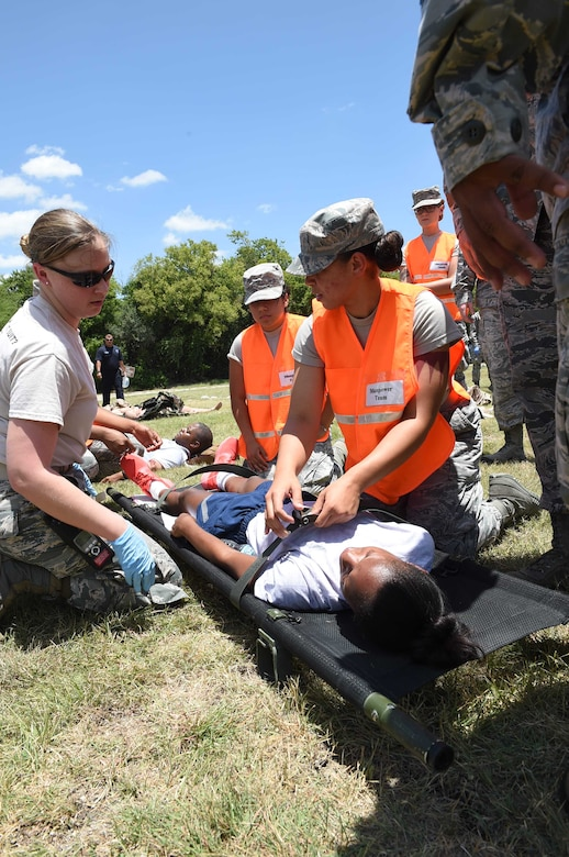 Members of the 59th Medical Wing disaster response team secure a patient to a litter prior to transport during a July 13, 2016 exercise at Camp Bramble on Joint Base San Antonio-Lackland, Texas. More than 50 Airmen participated in the exercise, which simulated an aircraft crash designed to test the team's ability to respond and treat patients in the event of a real-world incident. (U.S. Air Force photo/Staff Sgt. Jerilyn Quintanilla)