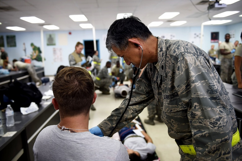 Lt. Col. Eddie Uy, a 59th Medical Wing staff pediatrician, examines a patient with simulated injuries during the July 13, 2016 disaster response exercise at Camp Bramble on Joint Base San Antonio-Lackland, Texas. The exercise, which simulated an aircraft crash, was designed to test the medics' response skills in the event of a similar real-world incident. (U.S. Air Force photo/Staff Sgt. Jerilyn Quintanilla)