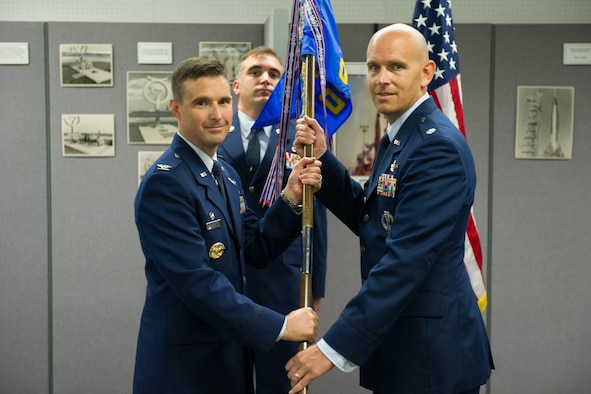 Col. Burton Catledge, 45th Operations Group commander, presents Lt. Col. Robert Shrader, 45th Operations Support Squadron commander, with a guidon during a change of command ceremony July 15, 2016, at Cape Canaveral Air Force Station, Fla. Changes of command are a military tradition representing the transfer of responsibilities from the presiding official to the upcoming official. (U.S. Air Force photo/Benjamin Thacker)
