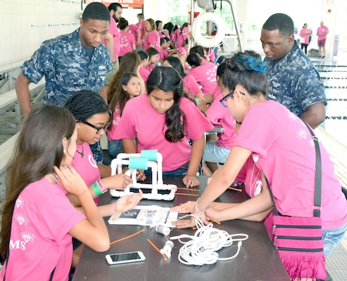 Navy recruiters, Machinist's Mate 2nd Class Deron Davis of Navy Recruiting Station (NRS) Hollywood Park and Aviation Boatswain's Mate 2nd Class Benjamin Brown of NRS De Zavala observe middle school girls assemble an underwater remotely operated vehicle (ROV) during a SeaPerch Competition held at the Ann Barshop Natatorium on the campus of the University of the Incarnate Word as a part of the miniGEMS (Girls in Engineering, Math and Sciences) program.  SeaPerch is an innovative underwater robotics program that equips teachers and students with the resources they need to build an underwater ROV in an in-school or out-of-school setting.  Davis, a native of Nacogdoches, Texas, is a graduate of Chireno High School in Chireno, Texas, and Brown, a native of Albany, Ga., graduated from Westover High School.  (U.S. Navy Photo by Burrell Parmer, Navy Recruiting District San Antonio Public Affairs/Released)