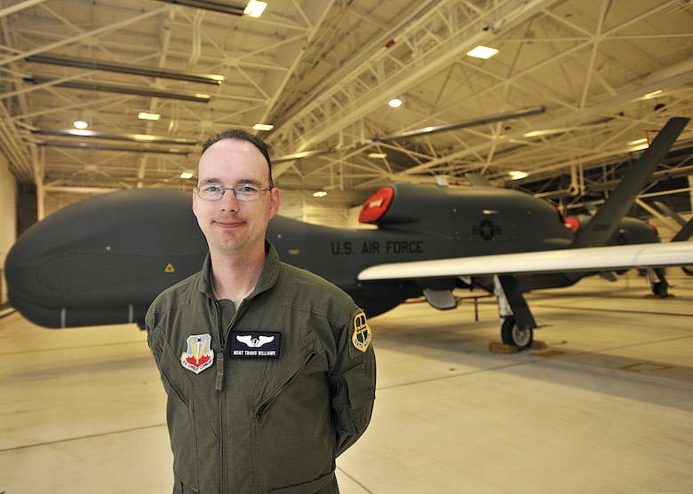 Master Sgt. Travis Williams, 69th Reconnaissance Group NCO-in-charge of group standards and evaluations, stands in front of an RQ-4 Global Hawk July 15, 2016, on Grand Forks Air Force Base, N.D. Williams is one of the 10 enlisted members who will go into Enlisted Pilot Initial Class in October 2016.  (U.S. Air Force photo by Senior Airman Xavier Navarro/Released)