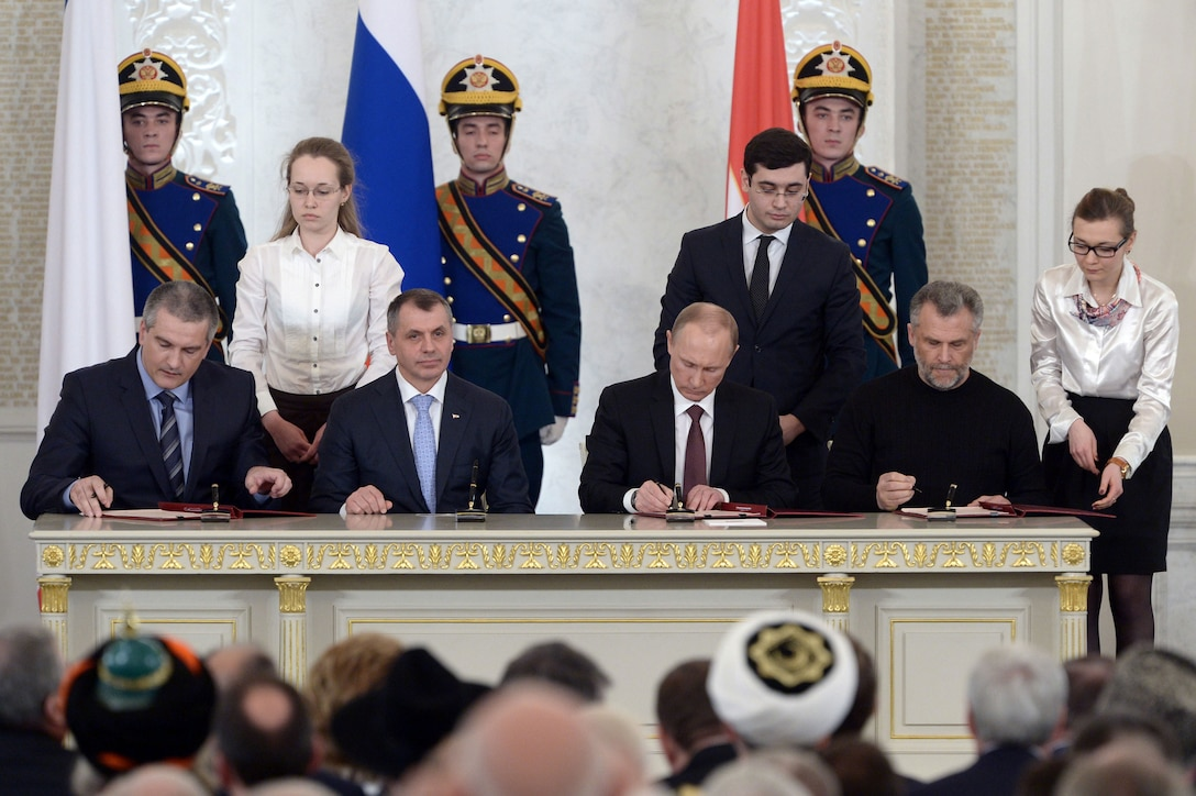 Leaders from Russia and Crimea sign the treaty of accession, completing the annexation of Crimea on March 18, 2014.