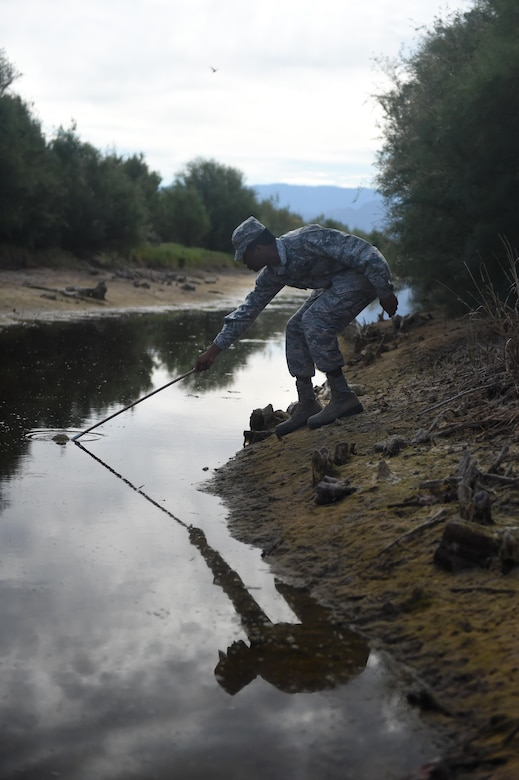 Airman 1st Class James, a 49th Civil Engineer Squadron pest management specialist, collects a water sample with mosquito larvae at Holloman Air Force Base, N.M., on July 7. Pest management personnel conduct pest management surveys, and determine actions needed to control infestations of plant and animal pests. (Last names are being withheld due to operational requirements. U.S. Air Force photo by Staff Sgt. Eboni Prince)