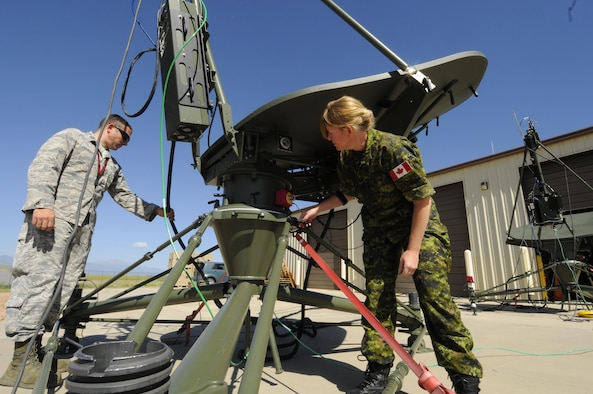 Capt. Dustyn Carroll, 527th Space Aggressors Squadron Aggressor Training flight commander, and Maj. Sheri Lattemore, assistant director of operations and Canadian liason officer to the 527th, set up a ground multi-band terminal antenna outside the 527 SAS's facility at Schriever Air Force Base, Colorado, Tuesday, July 11, 2016. The 527 SAS and 26th Space Aggressors Squadrons are the only Space Aggressors in the Department of Defense. (U.S. Air Force photo/2nd Lt. Darren Domingo)
