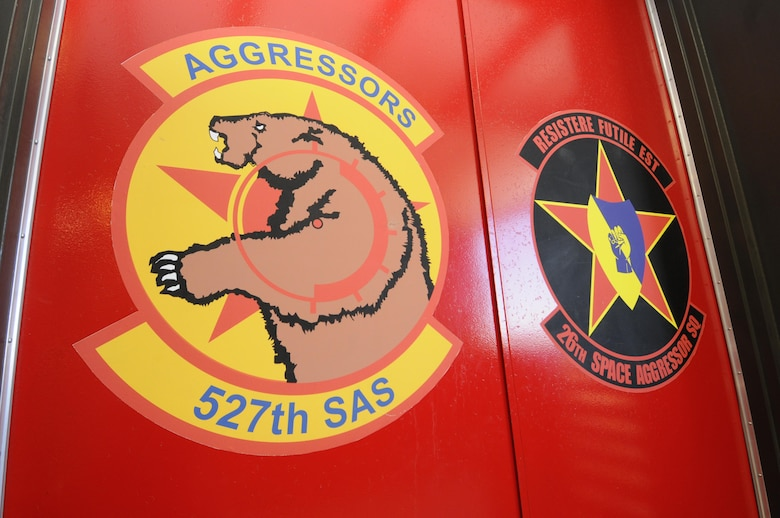 The 527th Space Aggressors Squadron and 26th Space Aggressors Squadron emblems are painted side by side on doors inside the Space Aggressors' facility at Schriever Air Force Base, Colorado. Currently, the Space Aggressors replicate live GPS and SATCOM electronic attack for training audiences across the globe.  (U.S. Air Force photo/2nd Lt. Darren Domingo)