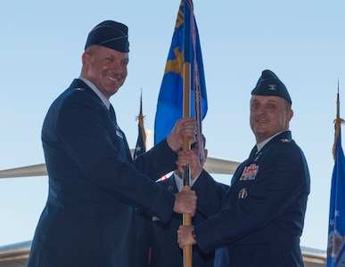Col. Craig Lambert, 628th Medical Group commander, receives the 628th MDG guidon from Col. Robert Lyman, Joint Base Charleston commander, during a change of command ceremony in Nose Dock 2 at JB Charleston, July 14, 2016. Lambert served as the Chief, Medical Support Division and Command Administrator, Office of the Command Surgeon, Air Force Global Strike Command for Barksdale Air Force Base, La. (U.S. Air Force Photo/Airman Megan Munoz)