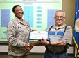 72nd Air Base Wing Commander Col. Stephanie Wilson presents retired Chief Master Sgt. Jesse Guiterrez with a certificate/award for the 2015 Retiree Volunteer of the Year Commendation. Chief Guiterrez has volunteered in the Tinker Clinic pharmacy for over 20 years. (Air Force photo by Kelly White)