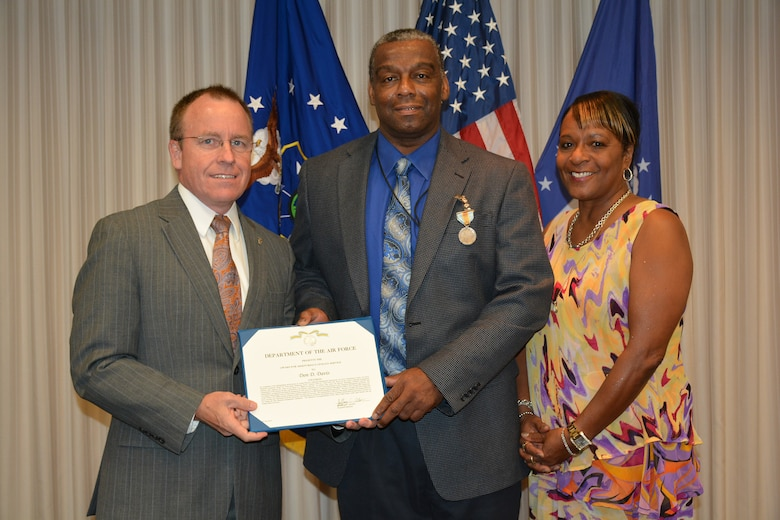 Jeffrey Allen, Air Force Sustainment Center executive director, left, presented Don Davis, AFSC Financial Management Directorate deputy director, with the Meritorious Civilian Service Medal prior to the June 7 AFSC staff meeting. Joining Mr. Davis for the presentation was his wife, Charlotte. (Air Force photo by Darren D. Heusel)
