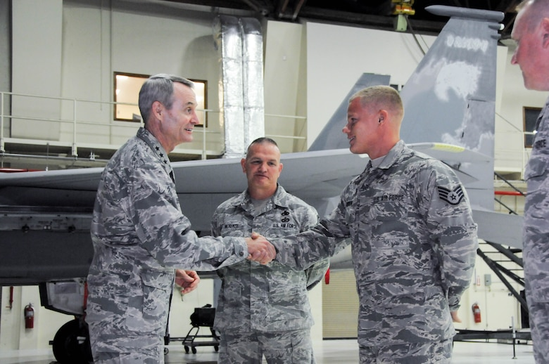 U.S. Air Force Lt. Gen. Darryl Roberson, commander of Air Education and Training Command, coins Staff Sgt. Christopher Robinson, 173rd Maintenance Group, July 7, 2016,in recognition of his superior performance at Kingsley Field, Ore. Roberson had a firsthand look at the unit's mission and capabilities, which includes training F-15C Eagle fighter pilots. The 173rd FW is aligned under AETC. (U.S. Air National Guard photo by Staff Sgt. Penny Snoozy)