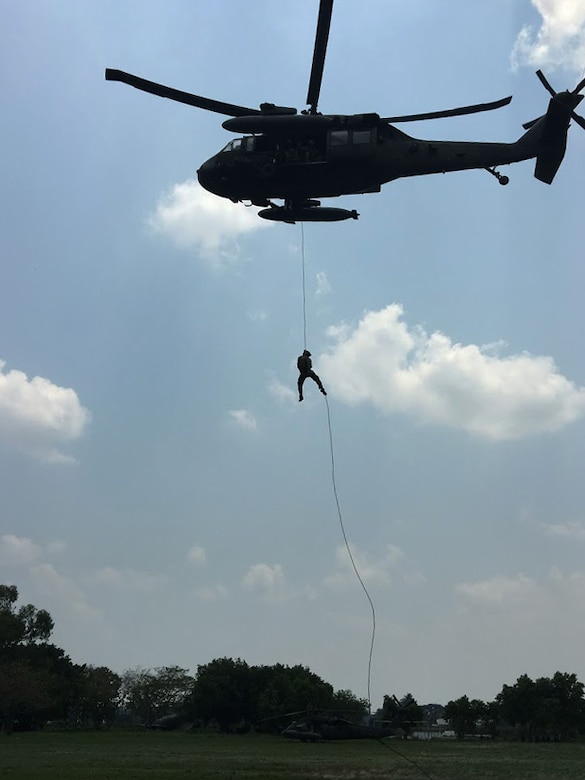 Members of the 1st Battalion, 228th Aviation Regiment from Joint Task Force-Bravo and Special Operations Command South conduct Fast Rope Insertion and Extraction System training from a UH-60 Black Hawk helicopter with Salvadorian military May 24 in El Salvador. JTF-Bravo and other U.S. Military elements, under the auspices of U.S. Southern Command, routinely conduct combined training and exercises with Partner Nation security forces in multiple Central American nations, improving the safety and security in the CENTAM region and southern approaches to the United States. According USSOUTHCOM officials, Salvadorian forces exemplify the command's security cooperation objectives to enhance the capability of partners to operate successfully in contingency, peacekeeping, humanitarian, disaster and stability operations. (Courtesy Photo)