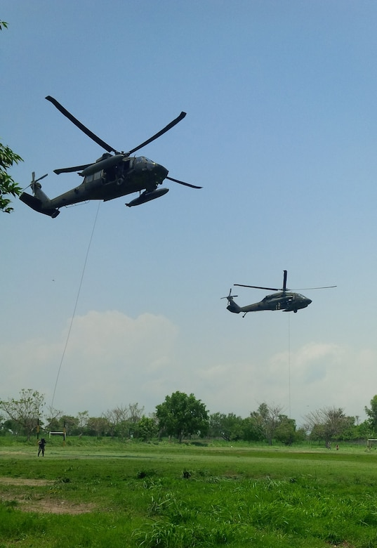 Members of the 1st Battalion, 228th Aviation Regiment from Joint Task Force-Bravo and Special Operations Command South conduct Fast Rope Insertion and Extraction System training from a UH-60 Black Hawk helicopter with Salvadorian military May 24 in El Salvador. Salvadorian military members received incremental training that began with helicopter familiarization and progressed to rappelling from, and being hoisted into, the 1-228th AVN's Black Hawks flying at heights of up to 90 feet. This training is crucial to both U.S. and Salvadorian military members' ability to safely conduct aerial operations for a variety of missions that include search and rescue, humanitarian aid and disaster relief, troop movements, counter-transnational organized crime operations and even firefighting efforts. (Courtesy Photo)