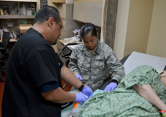 Rodrigo Bautista, health technician (near), Naval Medical Center San Diego, and Staff Sgt. Megan Gionti, medical technician, 117th Medical Group, sanitize a patient's wound in the Naval Medical Center San Diego Wound Care Clinic, in San Diego, Calif., June 27, 2016.  The 117 MDG trained with the U.S. Navy at Naval Medical Center San Diego.  The training included Airmen being implemented in real world U.S. Naval operations.  (U.S. Air National Guard photo by Staff Sgt. Jeremy Farson/Released)