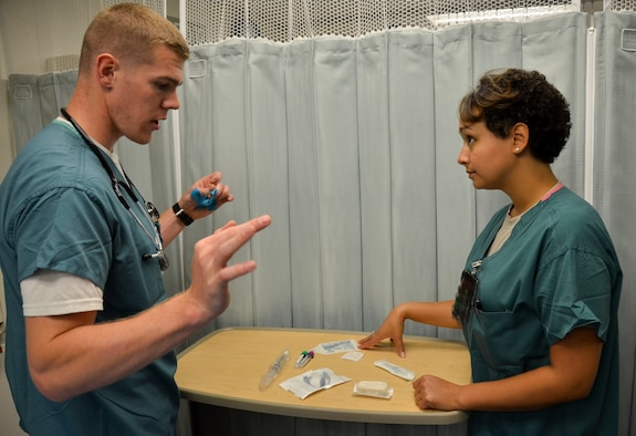 Staff Sgt. Stephanie M. Ford (right), medical technician, 117th Medical Group, discusses a procedure at the Naval Medical Center San Diego, in San Diego, Calif., June 23, 2016.  The 117 MDG trained with the U.S. Navy at Naval Medical Center San Diego.  The training included Airmen being implemented in real world U.S. Naval operations.  (U.S. Air National Guard photo by Staff Sgt. Jeremy Farson/Released)
