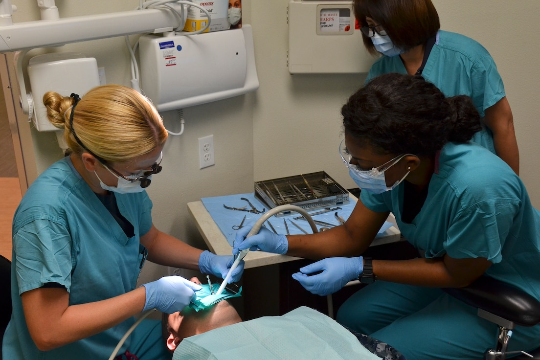 Airman 1st Class Franchestar Witherspoon (right), dental technician, 117th Medical Group assists Lt. Cmdr. Sara Chilcutt, fleet liason officer, Naval Branch Health Clinic, Naval Station San Diego in providing a dental procedure to a patient in the clinic, in San Diego, Calif., June 23, 2016.  The 117 MDG trained with the U.S. Navy at Naval Medical Center San Diego.  The training included Airmen being implemented in real world U.S. Naval operations.  (U.S. Air National Guard photo by Staff Sgt. Jeremy Farson/Released)