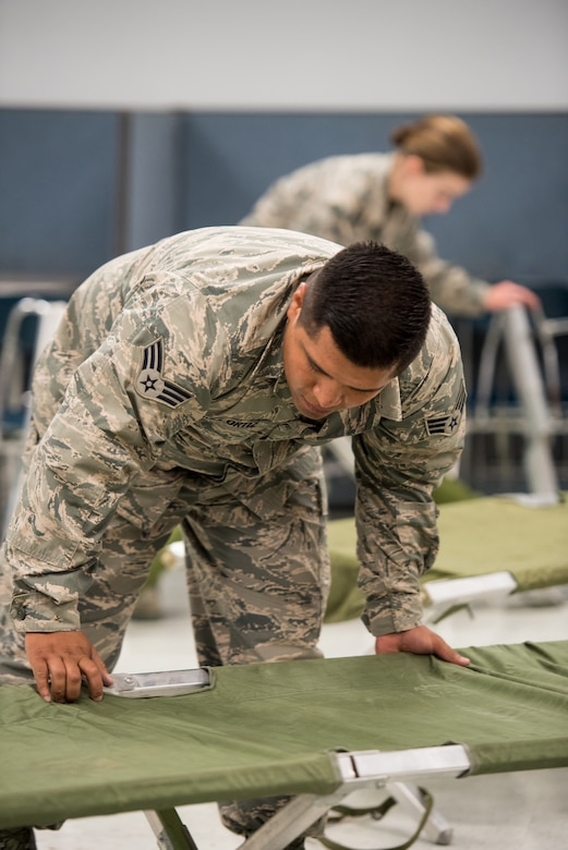 Senior Airman Nanstacio Perez-Ortiz, a food services specialist for the New Jersey Air National Guard's 108th Force Support Squadron, sets up cots for incoming military members at Graves County High School in Mayfield, Ky., July 15, 2016, in preparation for Bluegrass Medical Innovative Readiness Training. The program will offer medical and dental care at no cost to residents in three Western Kentucky locations from July 18 to 27. (U.S. Air National Guard photo by Master Sgt. Phil Speck)