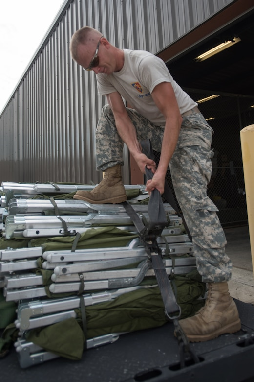 Sgt. Joseph Foriest, a transportation specialist for the Kentucky Army National Guard's 149th Brigade Support Battalion, tightens down straps across cots at Barkley Regional Airport in Paducah, Ky., July 14, 2016, in preparation for Bluegrass Medical Innovative Readiness Training. The program will offer medical and dental care at no cost to residents in three Western Kentucky locations from July 18 to 27. (U.S. Air National Guard photo by Master Sgt. Phil Speck)