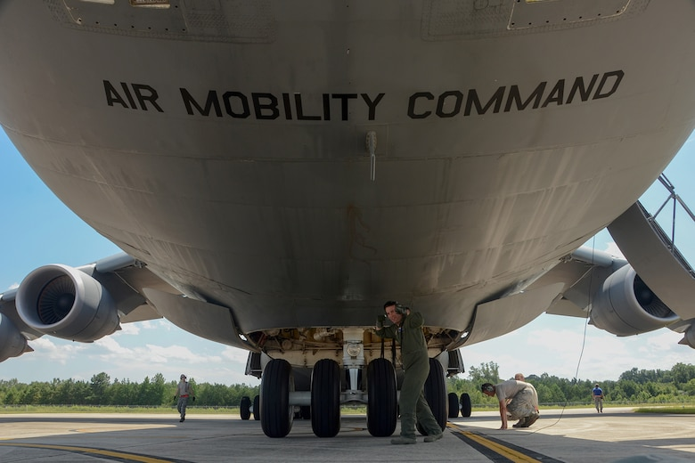 U.S. Air Force Tech. Sgt. Jake Schlemmer, a flight engineer assigned to the 709th Airlift Squadron, poses under a U.S. Air Force Lockheed C-5 Galaxy transport aircraft at McEntire Joint National Guard Base, S.C., July 8, 2016. Approximately 300 U.S. Airmen and 12 F-16 Fighting Falcon jets from the 169th Fighter Wing at McEntire JNGB, S.C., are deploying to Osan Air Base, Republic of Korea, as the 157th Expeditionary Fighter Squadron in support of the U.S. Pacific Command Theater Security Package. (U.S. Air National Guard photo by Airman 1st Class Megan Floyd)