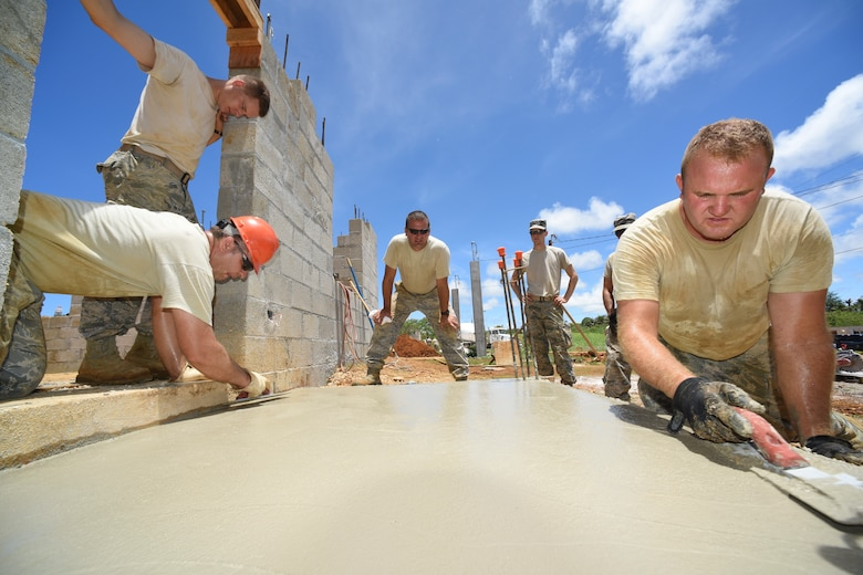 Maj. Jody W. Page, 114th Civil Engineer Squadron commander, oversees Airmen screeding a front porch concrete slab during the third phase of a multi project house build for Habitat for Humanity of Guam(HFHG), Inarajan, July 14, 2016. Airmen from the 114th Fighter Wing deployed to the Island of Guam to gain real world construction training as they assisted HFHG on the construction of two single family homes. (U.S. Air National Guard photo by Staff Sgt. Luke Olson/Released)