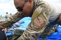 A parachute rigger with the 320th Special Tactics Squadron re-packs a parachute after a multi-aircraft, joint airborne operation with special operations assets and conventional forces from all four branches of the U.S. Armed Forces as part of Rim of the Pacific (RIMPAC) 2016 to strengthen their relationships and interoperability with their partners, Pohakuloa Training Area, Hawaii, July 14, 2016. The world's largest international maritime exercise, RIMPAC provides a unique training opportunity that helps participants foster and sustain the cooperative relationships that are critical to ensuring the safety of sea lanes and security on the world's oceans. (U.S. Air Force photo by 2nd Lt. Jaclyn Pienkowski/Released)