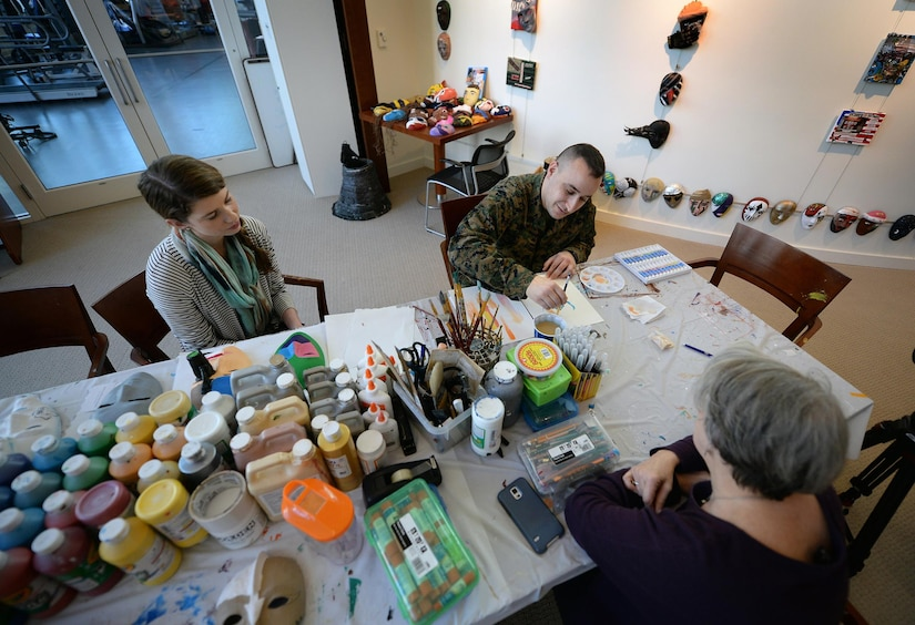 Marine Corps Staff Sgt. Anthony Mannino performs art therapy with guidance from Adrienne Stamper, art therapy intern as part of his traumatic brain injury treatment and recovery at the National Intrepid Center of Excellence in Bethesda, Md., March 1, 2016. DoD photo by Marvin Lynchard