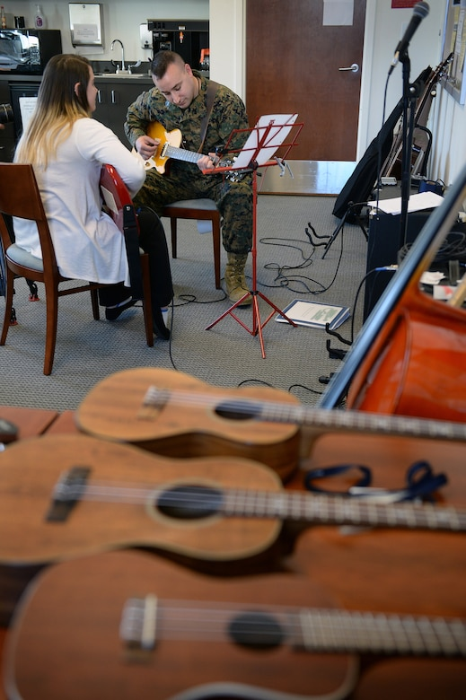 Marine Corps Staff Sgt. Anthony Mannino plays guitar as part of his traumatic brain injury treatment and recovery, with guidance form music therapy intern Kalli Jermyn at the National Intrepid Center of Excellence in Bethesda, Md., March 1, 2016. DoD photo by Marvin Lynchard