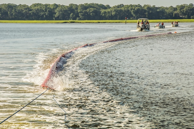 Marines and civilian personnel tow a boom in to place to contain a simulated oil spill aboard Marine Corps Air Station Beaufort July 13. The boom is towed behind the boats and acts as a large net, trapping the oil to be collected by a skimmer boat. The Marines are from various units within the air station and civilians are the Natural Resources Environmental Affairs Office.