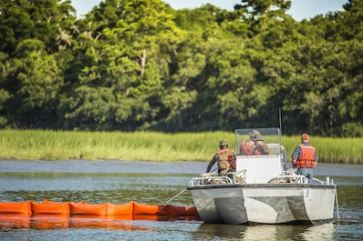 Marines and civilian personnel set a boom to contain a simulated oil spill aboard Marine Corps Air Station Beaufort July 13. The boom is towed behind the boats and acts as a large net, trapping the oil to be collected by a skimmer boat. Both Marines and civilians are part of the Facility Response Team for MCAS Beaufort and trained together to respond in case of a real spill. The Marines are with air station fuels and the civilians are with the Natural Resources Environmental Affairs Office.