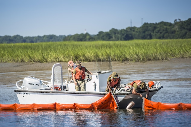 Marines and civilian personnel use a boom to contain a simulated oil spill aboard Marine Corps Air Station Beaufort July 13. The boom is towed behind the boats and acts as a large net, trapping the oil to be collected by a skimmer boat. The Marines are with the air station fuels section and the civilians are with the Natural Resources Environmental Affairs Office.