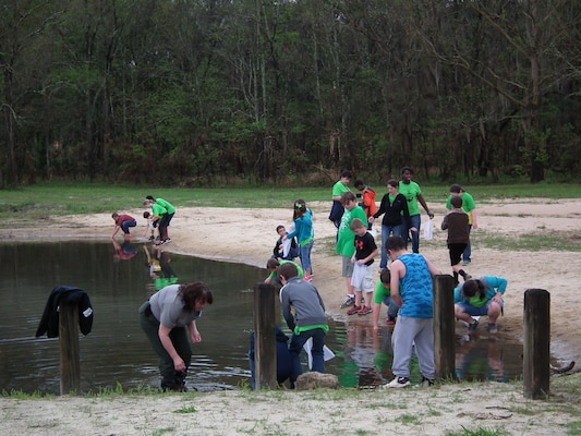 Park Ranger Angela Griffin assists the Sneads Elementary fourth graders as they collect tadpoles at the Every Kid in a Park fieldtrip at Lake Seminole