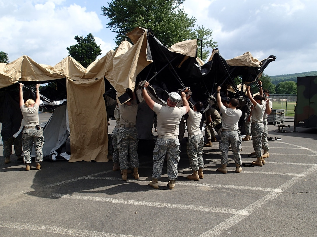Soldiers from Company A, 48th Combat Support Hospital out of Fort Story, Va., prepare tents for veterinary services during Greater Chenango Cares July 14, 2016. Greater Chenango Cares is one of the Innovative Readiness Training missions which provides real-world training in a joint civil-military environment while delivering world-class medical care to the people of Chenango County, N.Y., from July 15-24.