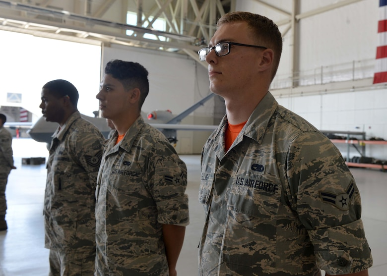 Airmen from the 432nd Aircraft Maintenance Squadron stand at parade rest during the Load Crew of the Quarter competition July 1, 2016, at Creech Air Force Base, Nevada. Load competitions such as this are an integral part of tradition and promote camaraderie throughout the 432nd AMXS. (U.S. Air Force photo by Airman 1st Class Kristan Campbell/Released)