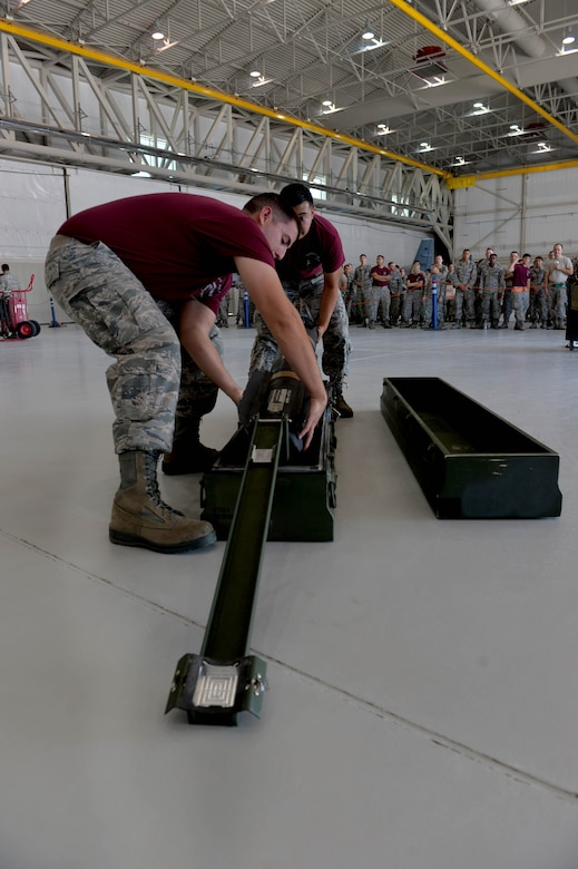 Senior Airman Dustin, 432nd Aircraft Maintenance Squadron load crew chief, and Airman 1st Class Gabriel, 432nd AMXS load crew member, perform a two man munitions movement July 1, 2016, at Creech Air Force Base, Nevada. Teams are given no knowledge of which munitions they will work with during the load, meaning that each team must visit the weapons standardization section to train and keep their skills sharpened for the competition. (U.S. Air Force photo by Airman 1st Class Kristan Campbell)