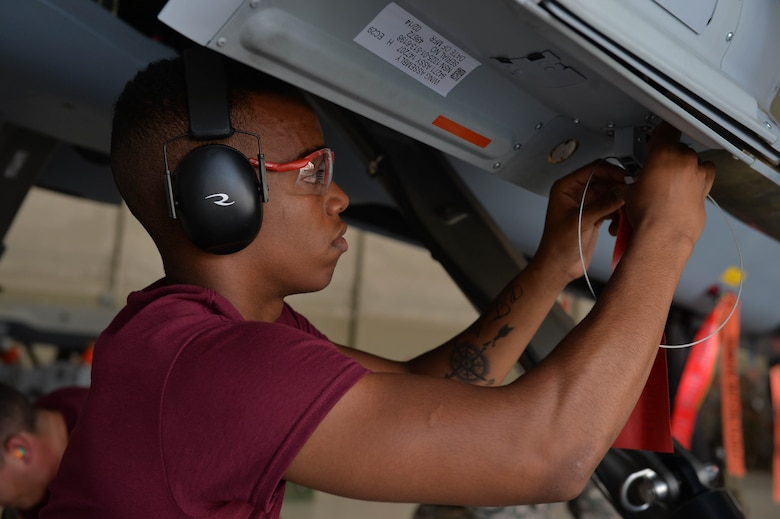 "Airman 1st Class Malik, 432nd Aircraft Maintenance Squadron load crew member, attaches a safety tag on an MQ-9 Reaper July 1, 2016, at Creech Air Force Base, Nevada. The tag, which reads ""remove before flight,"" is a safety measure used by aircrews to ensure safety during each step of a munitions load. (U.S. Air Force photo by Airman 1st Class Kristan Campbell/Released)"
