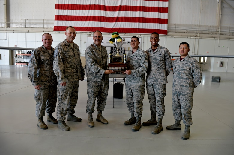 Airmen from the 432nd Aircraft Maintenance Squadron's Reaper Aircraft Maintenance Unit pose with leadership for a photo July 1, 2016, at Creech Air Force Base, Nevada. The winners of this quarter's Load Crew of the Quarter competition are Airman are: Senior Airman Dustin, 432nd AMXS load crew chief, Airman 1st Class Malik, 432nd AMXS load crew member, and Airman 1st Class Gabriel, 432nd AMXS load crew member.