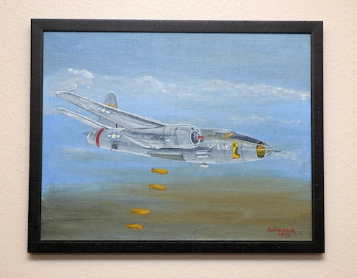 """""""Lady Eve,"""" a painting by Andrew Wieczorek, retired U.S. Air Force Master Sgt., hangs in the 37th Bomb Squadron at Ellsworth Air Force Base, S.D., July 14, 2016. Wieczorek, served as a ground crew member in the 37th BS with the U.S Army Air Corps, and was selected to paint nose art onto a B-26 Marauder known as the Lady Eve. The painting he created over five decades later of the aircraft was gifted to his old squadron and is now an artifact of its heritage. (U.S. Air Force photo by Airman Donald Knechtel/Released)"""