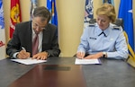 James Woolsey, Defense Acquisition University president, and Air Force Lt. Gen. Wendy Masiello, Defense Contract Management Agency director, sign a memorandum of agreement August 15 at DCMA's Fort Lee, Va., headquarters formalizing their organizations' continued strategic partnership through the College of Contract