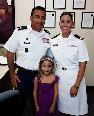 Navy Lt. j.g. Amy Aguirre (right, pictured as an Ensign) poses with her husband, Mario, and daughter, Isabella, after graduating from the Navy Reserve Basic Qualification Course for Supply Corps officers in 2014. Her husband retired as a colonel from the Army Reserves in January.