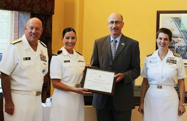 Navy Lt. j.g. Amy Aguirre (second from left, pictured as an Ensign), receives the Military Officers Association of America Professionalism Award in 2014 while attending the active duty Basic Qualification Course at the Navy Supply Corps School in Newport, R.I. Formerly a Navy Reserve Supply Corps Officer assigned to the Defense Contract Management Agency, Aguirre is one of three female reserve officers competitively selected to be recalled to active duty and serve in the Reserve Women in Submarines program.