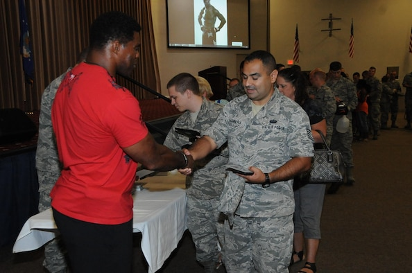 Airmen line up to meet Herschel Walker after he spoke to them about his battle with Dissociative Identity Disorder at Barksdale Air Force Base, La., July 12, 2016. Airmen brought footballs and other memorabilia for Walker, former NFL running back, to sign. (U.S. Air Force photo/Airman 1st Class Stuart Bright)