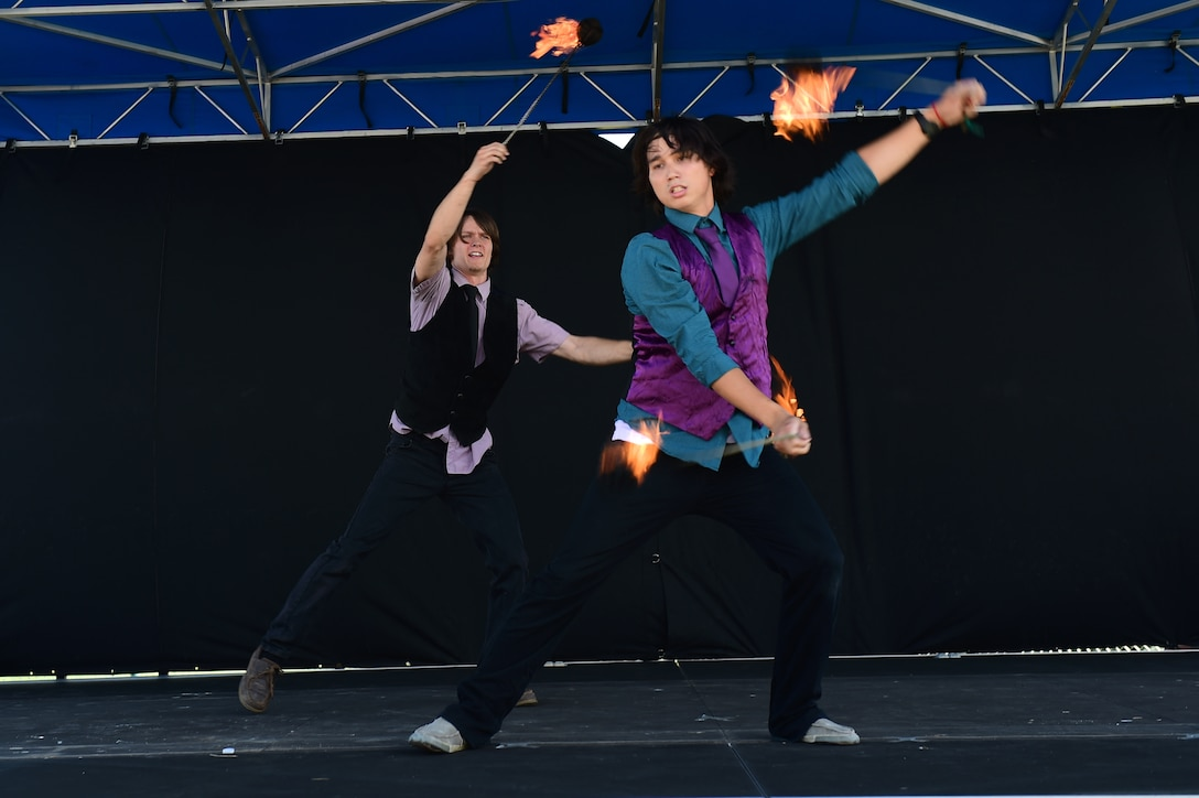 Tyler Chic and Xander Paris, Buckley Air Force Base youth, perform a fire-twirling routine July 15, 2016, during Diversity Day on Buckley Air Force Base, Colo. Diversity Day provided an opportunity to explore and celebrate the accomplishments and cultures of a diverse military force, which included food, dancing and music from various cultures. (U.S. Air Force photo by Airman 1st Class Gabrielle Spradling/Released)