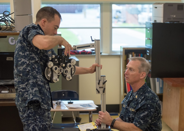 U.S. Navy Lt. Christopher Luft (left), an optometrist at Branch Health Clinic Navy Station Norfolk, and U.S. Navy Cmdr. Fred Kelley, an optometrist with Operational Health Support Unit Portsmouth Detachment M, setup optometry equipment at Paducah Tilghman High School in Paducah, Ky., July 17, 2016, in preparation for Bluegrass Medical Innovative Readiness Training. The program will offer medical and dental care at no cost to residents in three Western Kentucky locations from July 18 to 27.(U.S. Air National Guard photo by Master Sgt. Phil Speck)