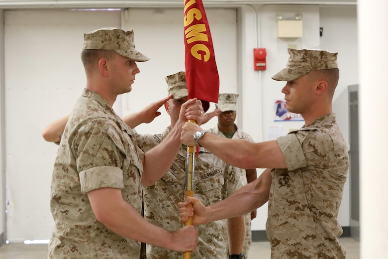 NAVAL SUPPORT FACILITY INDIAN HEAD, MD -- Capt. Lucas H. Forcella (right) passes the Headquarters and Service Company guidon to Capt. Robert G. Ukrainec during a change of command ceremony at Naval Support Facility Indian Head, Md., July 13, 2016. This Marine Corps drill movement symbolizes the passing of authority from outgoing to incoming company commander. (Official USMC Photo by Sgt. Jonathan S. Herrera/Released)