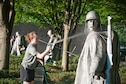 Senior Airman Katie Bobbitt, 459th Maintenance Squadron crew chief, uses a hose to wash a statue at the Korean War Veterans Memorial in Washington D.C., July 17, 2016. Members of the 459th Air Refueling Wing and their families volunteered to clean the memorial prior to its opening to the public for the day. (U.S. Air Force photo/Staff Sgt. Kat Justen)
