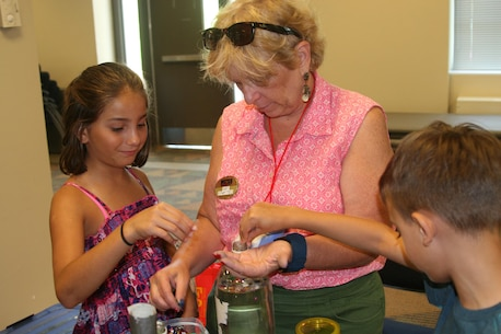 "Military children help Amy Watson, EFMP training, education, and outreach specialist, prepare a hurricane simulator at ""All About Weather"" on July 12."