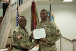 Former DLA Distribution commander Army Brig. Gen. Richard Dix, left, presents the Defense Meritorious Service Medal to Army Capt. Michael Thomas, aide-de-camp.