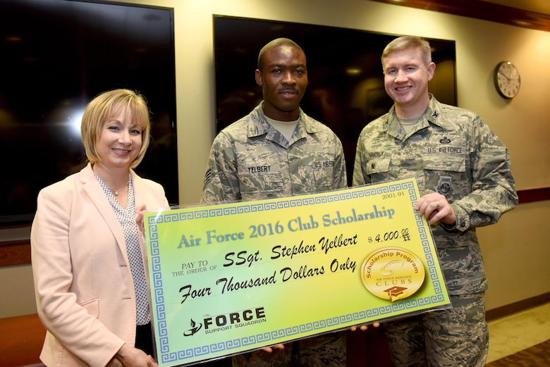 U.S. Air Force Col. Terry Hamrick, 17th Training Wing Vice Commander, and Toni Hansen, 17th Force Support Squadron Director, award Staff Sgt. Stephen Yelbert, , 17th Comptroller Squadron financial services technician and Non-Commissioned Officer in charge for reports and analysis, the Air Force 2016 Club Scholarship for 4,000 dollars at the Norma Brown Building on Goodfellow Air Force Base, Texas, June 28, 2016. Yelbert received 2nd place in the scholarship competition throughout the Air Force. (U.S. Air Force photo by Airman 1st Class Caelynn Ferguson/Released)