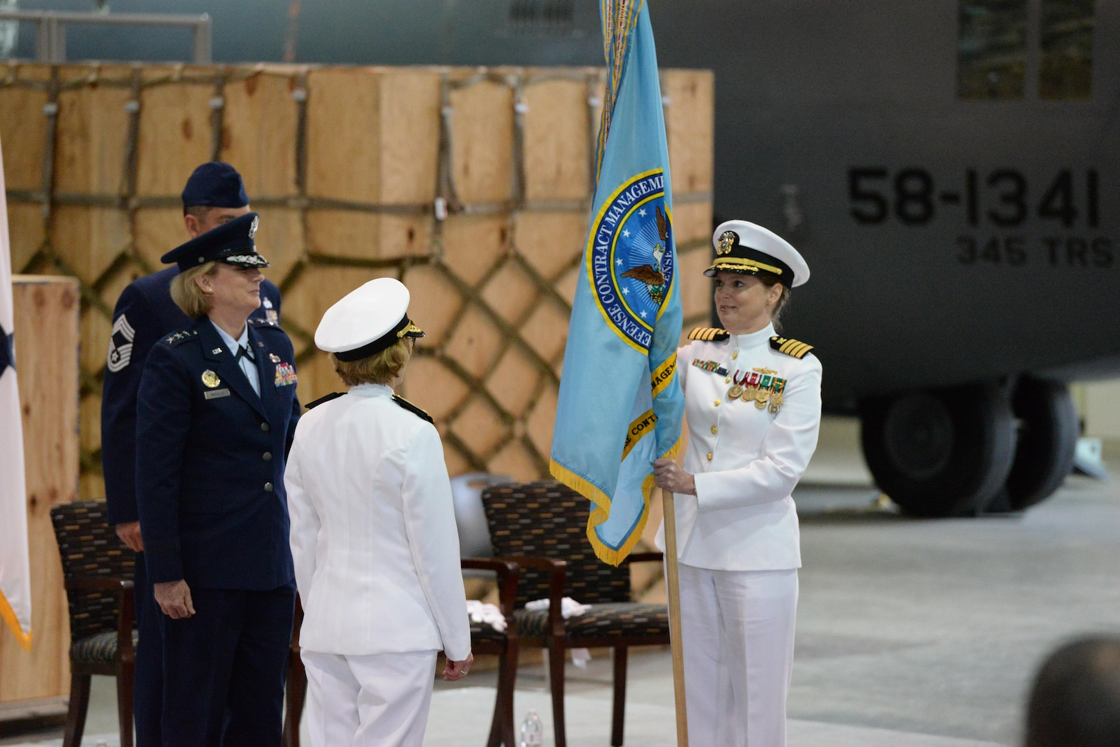 Navy Capt. Sonya Ebright receives the guidon from Navy Rear Adm. Deborah Haven, ceremonially marking the transfer of leadership of Defense Contract Management Agency International during a change of command ceremony at Fort Lee, Virginia, May 23. Ebright assumed command over the agency's international contract administration operations in 26 different countries overseeing 9,600 contracts totaling over $75 billion in program value.