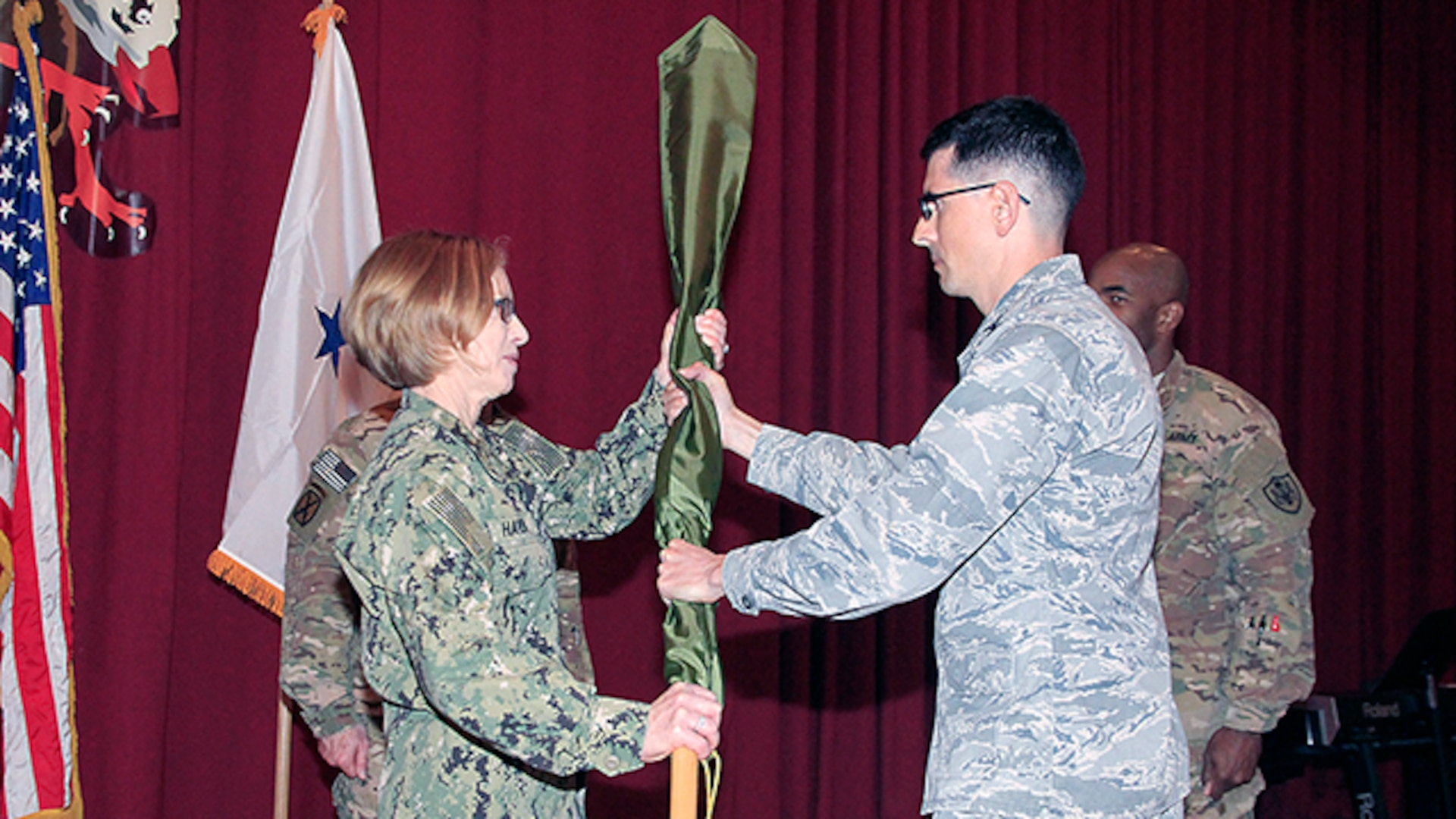 Air Force Col. Christopher Juarez, Defense Contract Management Agency Middle East commander, presents the cased colors of DCMA Afghanistan to Navy Rear Adm. Deborah Haven, DCMA International commander, during a casing ceremony marking the end of DCMA's mission in Afghanistan at Camp Arifjan, Kuwait, Jan. 14.